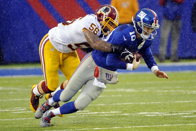 New York Giants quarterback Eli Manning (10) is sacked by Washington Redskins' Perry Riley (56) during the first half of an NFL football game Sunday, Dec. 29, 2013, in East Rutherford, N.J. (AP Photo/Bill Kostroun)