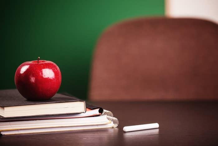 desk with books and an apple on top of it
