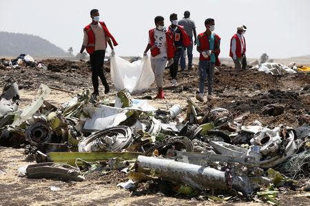 Ethiopian Red Cross workers carry a body bag with the remains of Ethiopian Airlines Flight ET 302 plane crash victims at the scene of a plane crash, near the town of Bishoftu, southeast of Addis Ababa