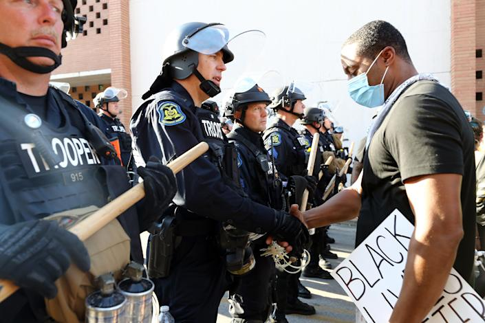 A demonstrator shakes hands with a police officer during a protest on May 31, 2020 in Kansas City, Missouri. (Photo by Jamie Squire/Getty Images)
