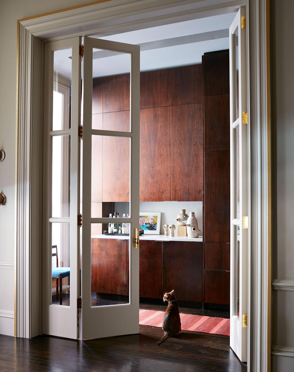 A view through French doors of the apartment's kitchen, whose cabinets are custom designed in walnut. Otero's contractor was from Simply Elegant.