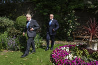 Britain's Prime Minister Boris Johnson, foreground, walks with Australian Prime Minister Scott Morrison after their meeting, in the garden of 10 Downing Streeet, in London, Tuesday June 15, 2021. Britain and Australia have agreed on a free trade deal that will be released later Tuesday, Australian Trade Minister Dan Tehan said. (Dominic Lipinski/Pool Photo via AP)