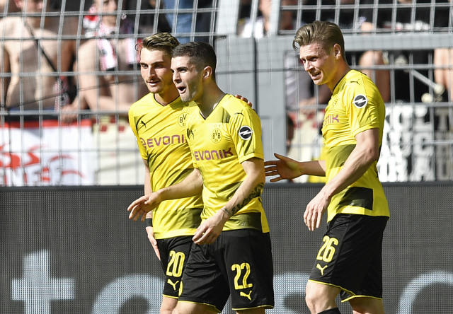 Dortmund's Christian Pulisic, center, reacts surprised after scoring during the German Bundesliga soccer match between Borussia Dortmund and VfB Stuttgart in Dortmund, Germany, Sunday, April 8, 2018. (AP Photo/Martin Meissner)