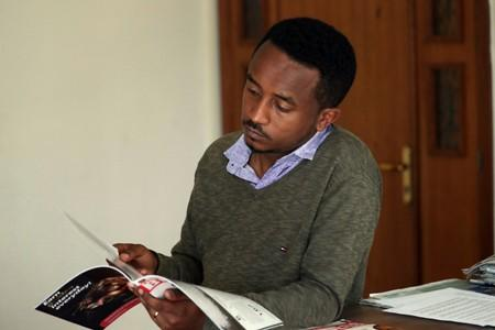 Eritrean refugee Berhane reads news magazine with cover photo of Ethiopian PM in Addis Ababa