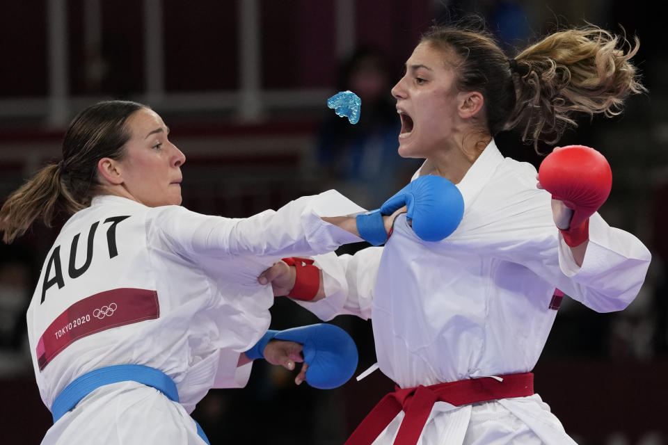 Ivet Goranova of Bulgaria, right, loses her mouth piece near Bettina Plank of Austria during the women's kumite -55kg semifinal bout for Karate at the 2020 Summer Olympics, Thursday, Aug. 5, 2021, in Tokyo, Japan. (AP Photo/Vincent Thian)
