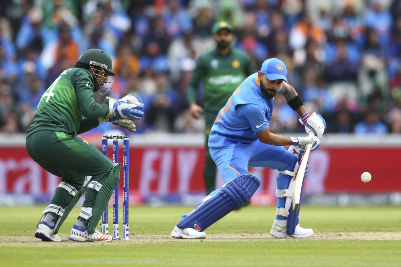 India's captain Virat Kohli, right, plays a shot under the watch of Pakistan's captain Sarfaraz Ahmed during the Cricket World Cup match between India and Pakistan at Old Trafford in Manchester, England, Sunday, June 16, 2019. (AP Photo/Dave Thompson)