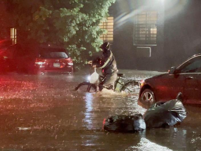 delivery driver on bicycle navigates ida floodwaters in nyc