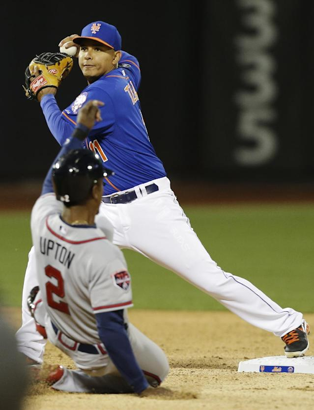 New York Mets shortstop Ruben Tejada, top, throws out Atlanta Braves' Freddie Freeman at first base after forcing out B.J. Upton (2) for a double play during the third inning of a baseball game on Friday, April 18, 2014, in New York. (AP Photo/Frank Franklin II)