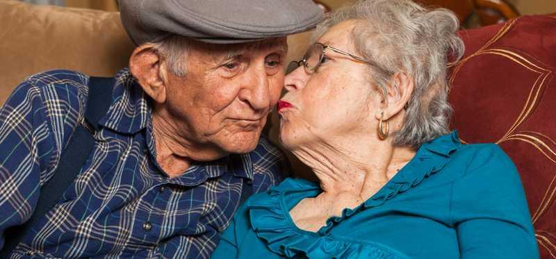 An elderly woman kisses her elderly husband on the cheek.