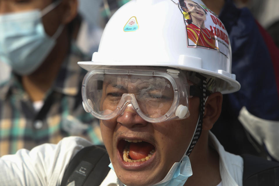A protester wears a safety helmet and eye protector as he shouts slogans during a protest against a military coup in Yangon, Myanmar, Sunday, Feb. 28, 2021. In the month since Feb. 1 coup, the mass protests occurring each day are a sharp reminder of the long and bloody struggle for democracy in a country where the military ruled directly for more than five decades. (AP Photo)