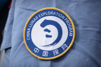 A patch for the China Lunar Exploration Program is displayed on the uniform of a worker at the Wenchang Space Launch Site in Wenchang in southern China's Hainan province, Monday, Nov. 23, 2020. Chinese technicians were making final preparations Monday for a mission to bring back material from the moon's surface for the first time in nearly half a century — an undertaking that could boost human understanding of the moon and of the solar system more generally. (AP Photo/Mark Schiefelbein)