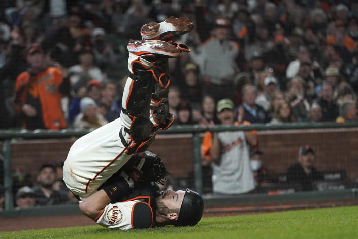 San Francisco Giants catcher Curt Casali falls backward after catching an out in foul territory hit by San Diego Padres' Fernando Tatis Jr. during the eighth inning of a baseball game in San Francisco, Monday, Sept. 13, 2021. (AP Photo/Jeff Chiu)