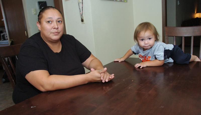 LuAnna Fox, seen here with one-year-old son Jerrico in this Aug. 9, 2012 photograph from the Northern Cheyenne Indian Reservation, is living temporarily with her family of eight in a sparsely-furnished duplex after the Ash Creek fire burned down their house in late June. (AP Photo/Matthew Brown)