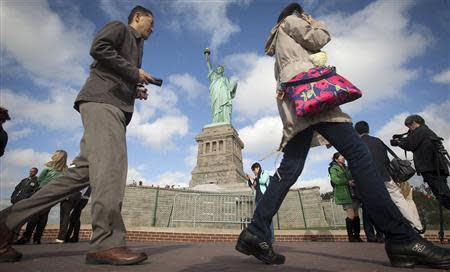 People walk past the Statue of Liberty on Liberty Island in New York, October 13, 2013. REUTERS/Carlo Allegri