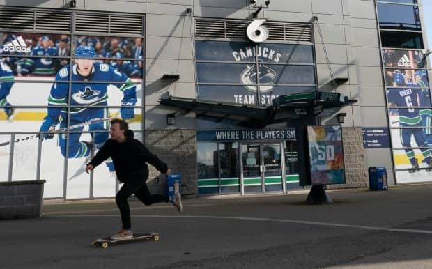 A skateboarder rides past a quiet Rogers Arena in downtown Vancouver last Thursday. (Jonathan Hayward/The Canadian Press - image credit)