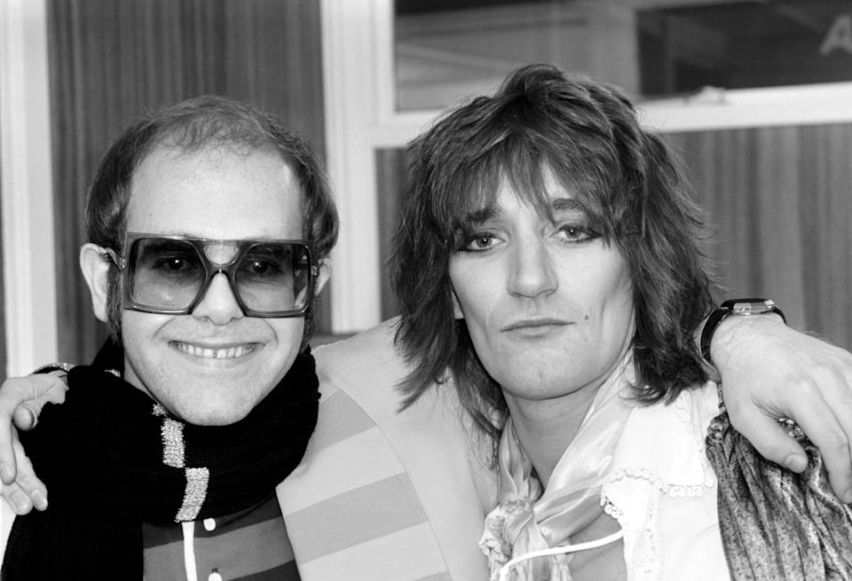 Pop superstars Rod Stewart and Elton John make it up back stage at Olympic tonight just before Rod went on stage for the third night of his series of London concerts. December 1976 76-07532-005 (Photo by WATFORD/Mirrorpix/Mirrorpix via Getty Images)