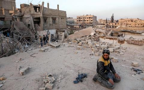 A Syrian civil defence volunteers performs ritual sunset prayers next to the site of a building that collapsed following reported regime air strikes in the rebel-held town of Arbin, in the besieged Eastern Ghouta - Credit: AFP