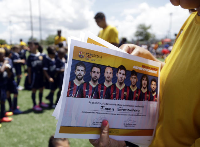 In this Thursday, Aug. 1, 2014 photo, certificates are sorted before being handed out to children at the end of a soccer camp held by FC Barcelona in Miami. European clubs like Barcelona, Liverpool and Arsenal have long sent coaches to work at U.S. summer camps, but now some are opening year-round U.S. academies aimed at finding new talent but also to expand their fan bases. This is part of a number of initiatives of major teams to grow their brands in the U.S. (AP Photo/Lynne Sladky)