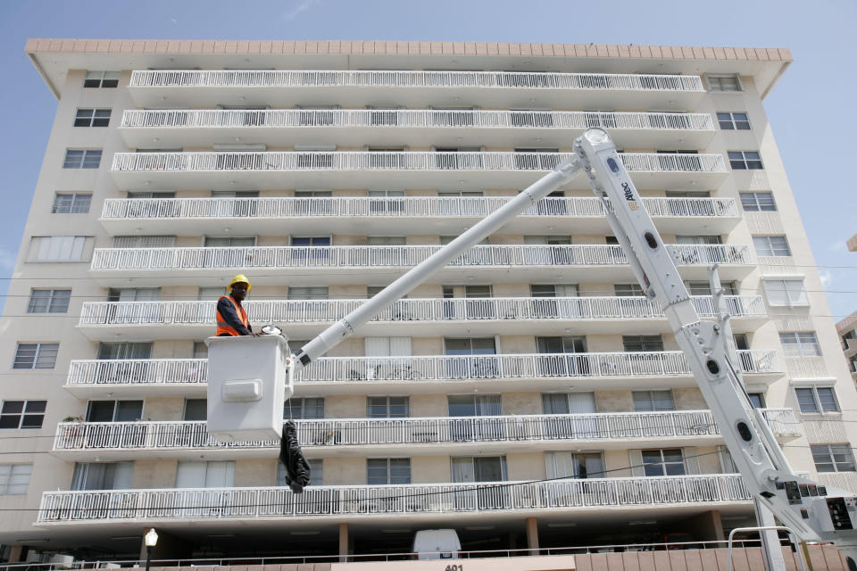 A construction worker in a lift bucket outside a condominium building in Miami, Florida. (Photo: Jeffrey Greenberg/UIG via Getty Images)
