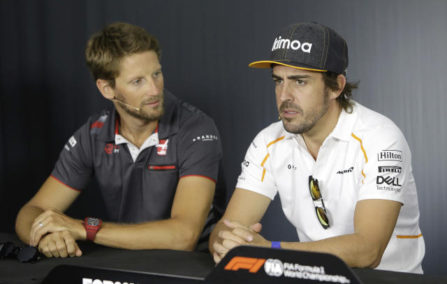 Haas driver Romain Grosjean of France, left, speaks with McLaren driver Fernando Alonso of Spain during a news conference at the Paul Ricard racetrack, in Le Castellet, southern France, Thursday, June 21, 2018. The Formula one race will be held on Sunday. (AP Photo/Claude Paris)