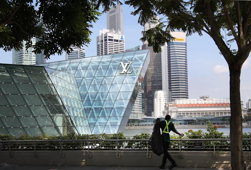 In this May 24, 2012 photo, a cleaner searches for trash among landscaping of a luxury mall and casino resort located just off the financial district of Singapore. Stagnant wages, weighed down by a flood of cheap foreign labor, are tearing at a social compact that has allowed the People's Action Party to govern Singapore almost unchallenged for five decades. (AP Photo/Wong Maye-E)
