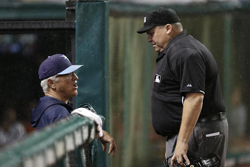 Tampa Bay Rays manager Joe Maddon, left, talks with home plate umpire Fieldin Culbreth about the rain falling in the second inning of a baseball game, Friday, May 31, 2013, in Cleveland. The game was delayed shortly thereafter. (AP Photo/Tony Dejak)