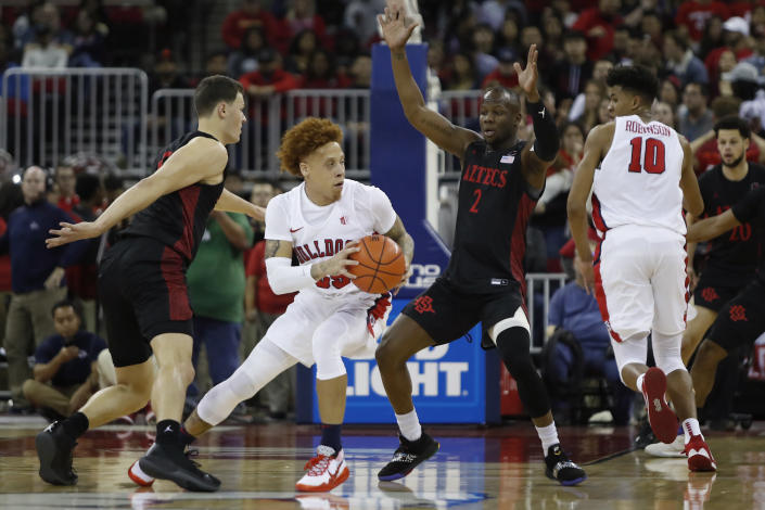 Fresno State's Noah Blackwell looks to drive on San Diego State's Adam Seiko, center right, during the first half of an NCAA college basketball game in Fresno, Calif., Tuesday Jan. 14, 2020. (AP Photo/Gary Kazanjian)