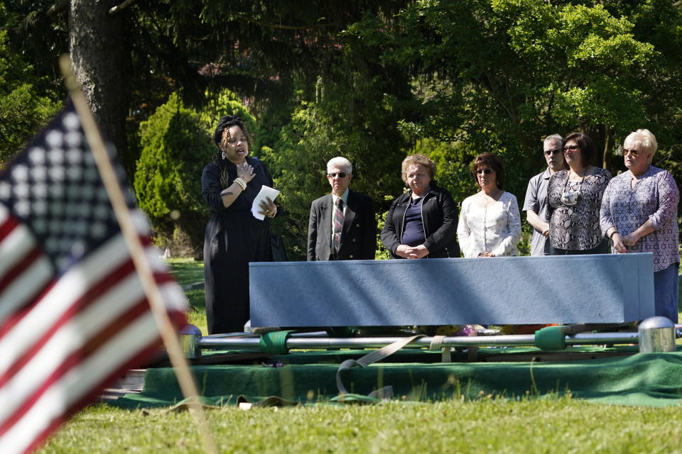 Edwina Frances Martin, Staten Island's public administrator of estates, left, says a few words during a burial of four people at a cemetery in the Staten Island borough of New York, Thursday, June 17, 2021. The deceased died during the coronavirus pandemic and were being stored at a temporary morgue in Brooklyn. The facility is out of sight and mind for many for many as the city celebrates its pandemic progress but stands as a reminder of the loss, upheaval and wrenching choices the virus inflicted in one of its deadliest U.S. hotspots. (AP Photo/Seth Wenig)
