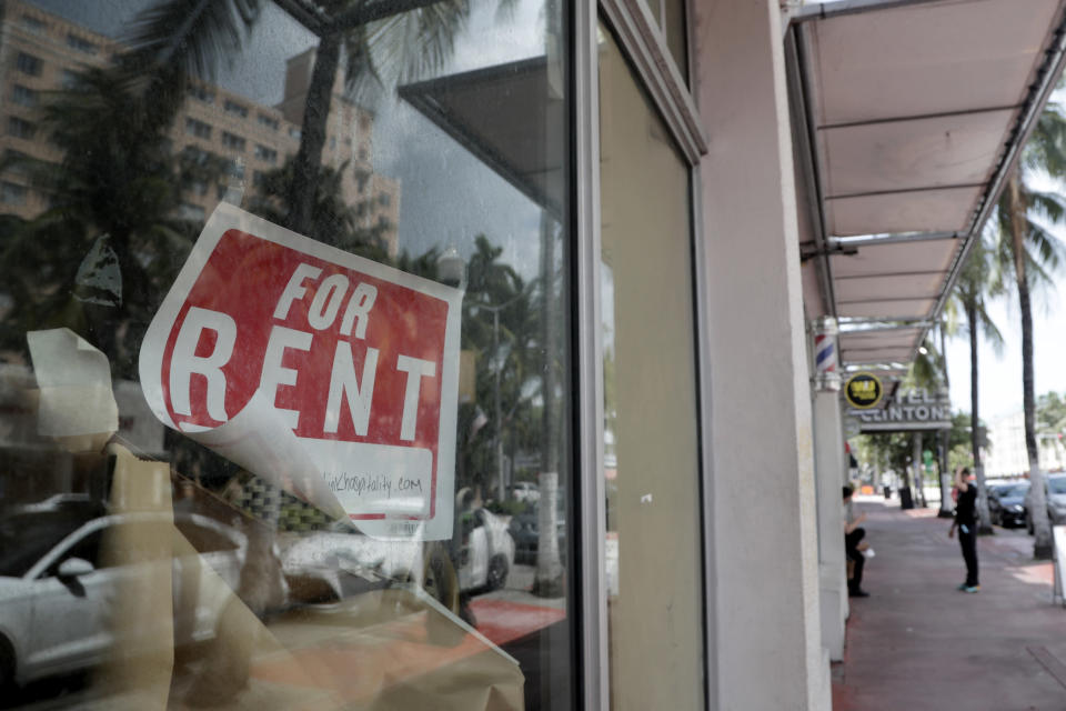 FILE - In this July 13, 2020, file photo a For Rent sign hangs on a closed shop during the coronavirus pandemic in Miami Beach, Fla. Nearly half of Americans whose families experienced layoffs during the pandemic now believe their lost jobs will not return, a new poll from The Associated Press-NORC Center for Public Affairs Research shows, as temporary layoffs give way to shuttered businesses, bankruptcies and lasting payroll cuts. (AP Photo/Lynne Sladky, File)