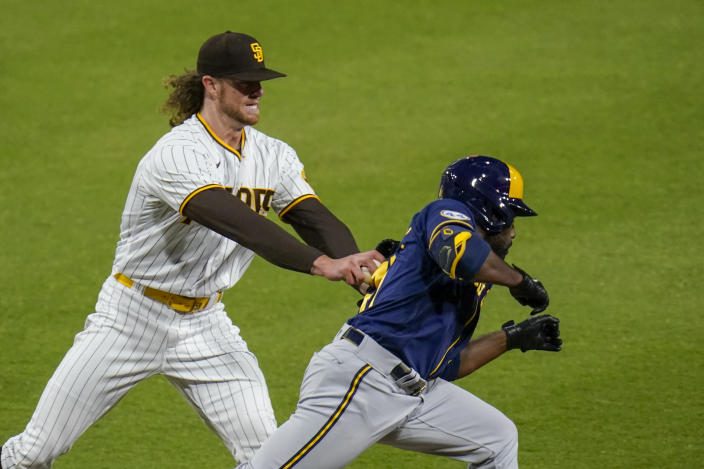 San Diego Padres starting pitcher Chris Paddack tags out Milwaukee Brewers' Jackie Bradley Jr. during the third inning of a baseball game Tuesday, April 20, 2021, in San Diego. (AP Photo/Gregory Bull)