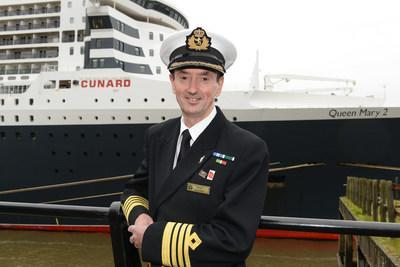 Cunard Captain Christopher Wells standing in front of flagship Queen Mary 2. As Wells embarked on his retirement this week, he was awarded the rank of Commodore in recognition of his 20 year career with the brand.
