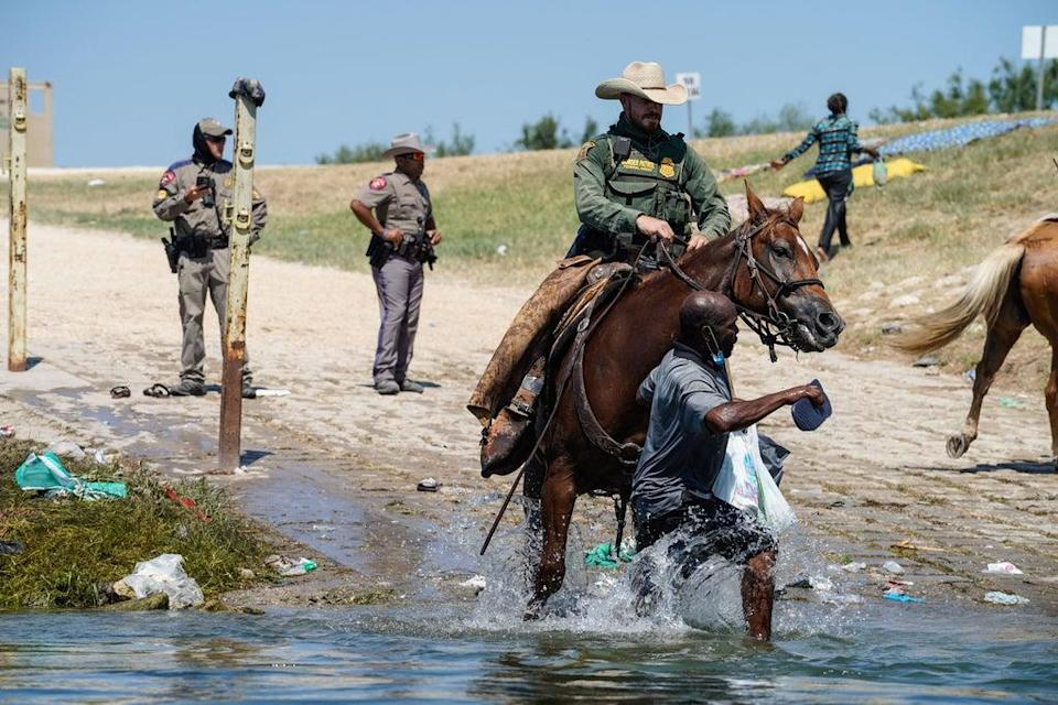 A United States Border Patrol agent on horseback tries to stop a Haitian migrant from entering an encampment on the banks of the Rio Grande near the Acuna Del Rio International Bridge in Del Rio, Texas on 19 September 2021 (AFP via Getty Images)