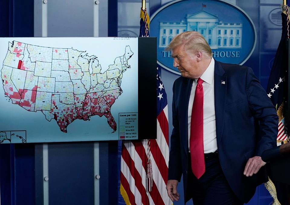 "President Donald Trump, who previously told the country that the coronavirus would disappear ""like a miracle,"" stands next to a map of his miracle on July 23. (Photo: Drew Angerer/Getty Images)"