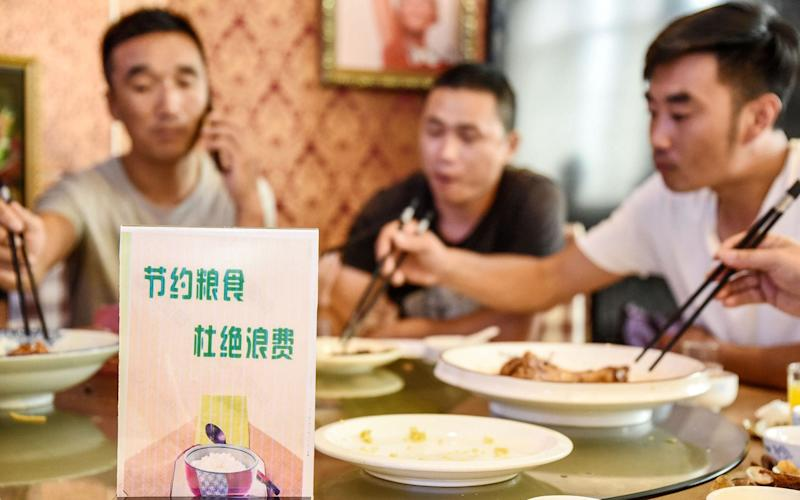 """A sign encouraging people not to waste food is seen at a restaurant in Handan. Chinese diners are being urged to order """"one less plate"""", after Chinese President Xi Jinping made a speech urging the nation to stop wasting food - STR/AFP"""