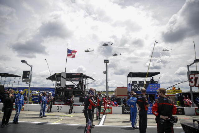 A flyover is watched by NASCAR drivers and crew members before a NASCAR Cup Series auto race at Atlanta Motor Speedway, Sunday, June 7, 2020, in Hampton, Ga. (AP Photo/Brynn Anderson)