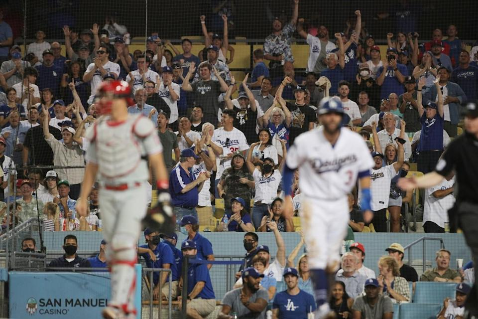 Fans cheer as Dodgers left fielder Chris Taylor scores on a double by pitcher Julio Urias.