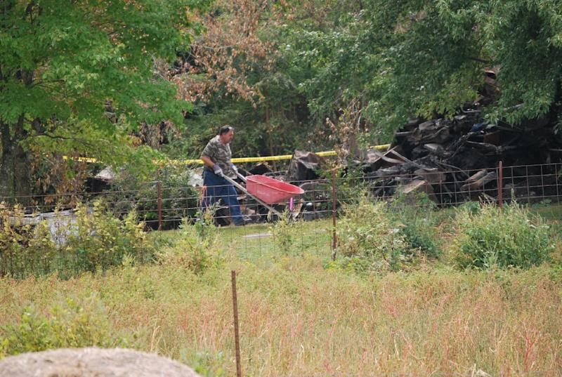 A worker moves a wheel barrel on Thursday, Sept. 27, 2012, near Shelbyville, Tenn., at the site of a house fire where an elderly couple and two young children lived. Authorities were searching the debris for the remains of the two missing children, 9-year-old Chloie Leverette and 7-year-old Gage Daniel. The two children were initially believed to have perished in the intense fire, which firefighters battled overnight Sunday and early Monday. (AP Photo/Kristin M. Hall)