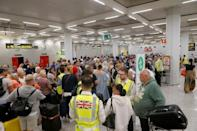 Passengers are seen at Thomas Cook check-in points at Mallorca Airport after the world's oldest travel firm collapsed, in Palma de Mallorca