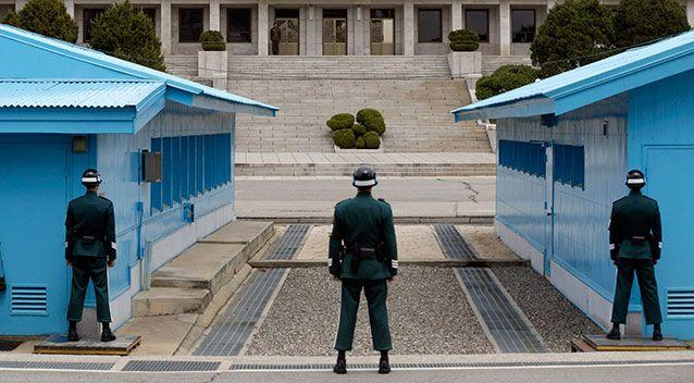 File image of a North Korean soldier, centre top, looks at the southern side as South Korean soldiers stand guard at the border village of Panmunjom. Picture: AAP