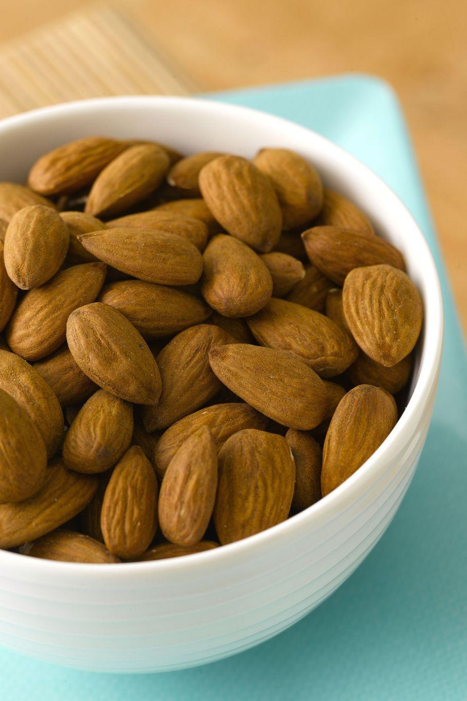 """<p>Just a handful of these and you'll be dozing off in no time. Pasquella says <a href=""""https://www.goodhousekeeping.com/health/diet-nutrition/a19503705/almonds-nutrition/"""" rel=""""nofollow noopener"""" target=""""_blank"""" data-ylk=""""slk:almonds"""" class=""""link rapid-noclick-resp"""">almonds</a> contain tryptophan and magnesium, which both help to naturally reduce muscle and nerve function while also steadying your heart rhythm. </p><p>Almond butter or <a href=""""https://www.goodhousekeeping.com/health/diet-nutrition/a26866/health-benefits-peanut-butter/"""" rel=""""nofollow noopener"""" target=""""_blank"""" data-ylk=""""slk:peanut butter"""" class=""""link rapid-noclick-resp"""">peanut butter</a> will also work. Spread it on graham crackers, a banana, or <a href=""""https://www.goodhousekeeping.com/food-recipes/cooking/a47114/sweet-potato-toast-trend/"""" rel=""""nofollow noopener"""" target=""""_blank"""" data-ylk=""""slk:that sweet potato toast"""" class=""""link rapid-noclick-resp"""">that sweet potato toast</a>. Again, keep your dollop under a tablespoon so you're not feeling too stuffed before heading to bed.</p>"""