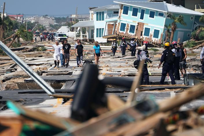 <p>First responders and residents walk along a main street following Hurricane Michael in Mexico Beach, Fla., Oct. 11, 2018. (Photo: Carlo Allegri/Reuters) </p>