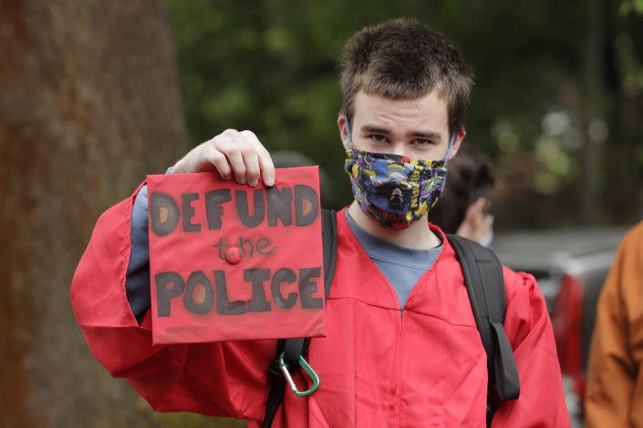 """Elliot Armitage, a 2020 graduate of Ballard High School, holds his mortarboard cap that reads """"Defund the Police"""" as he prepares to take part in a cap and gown Black Lives Matter march with other high school graduates, Monday, June 15, 2020, in Seattle. The theme of the march as """"Walking for Those Who Can't,"""" and organizers were calling for police funding reforms and an end to Seattle public schools' relationship with the Seattle Police Department. (AP Photo/Ted S. Warren)"""