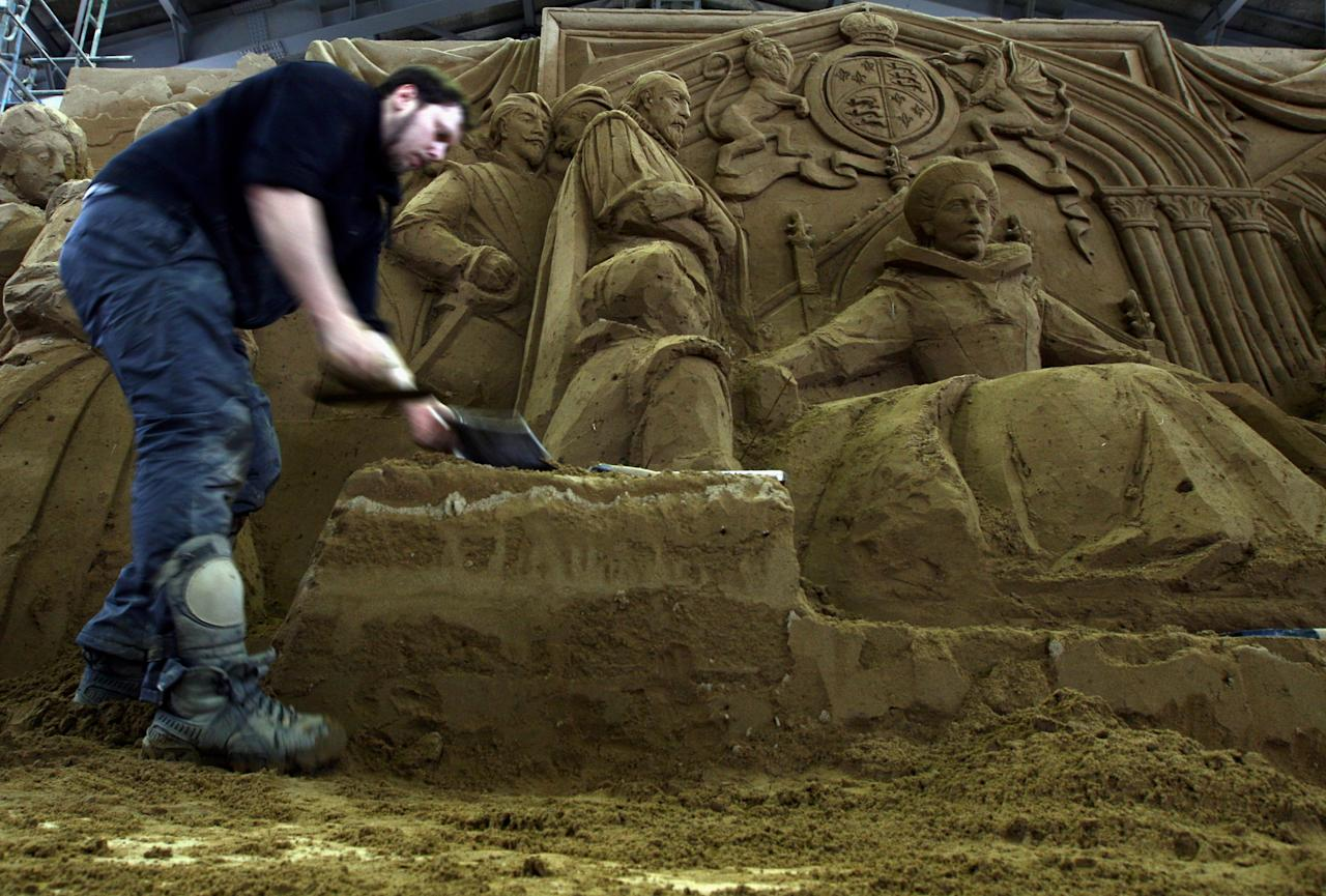 Ilya Filimontsev of Russia works on his sand replica titled 'Absolute Monarchism Under the Regime of Queen Elizabeth I' at Sand Museum located in the Tottori Dune on April 1, 2012 in Tottori, Japan. (Photo by Buddhika Weerasinghe/Getty Images)