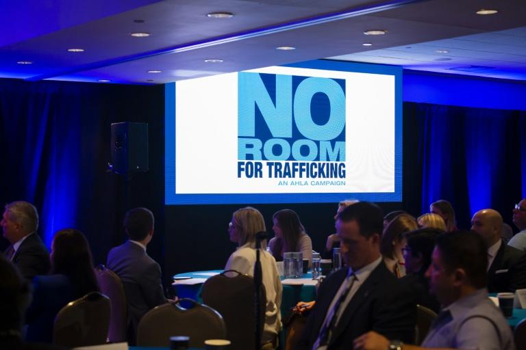'No Room for Trafficking' campaign logo is seen on a screen during a meeting to prevent human trafficking at Fontainbleu Miami Beach in Miami Beach on January 9, 2020 (AFP Photo/Eva Marie UZCATEGUI)