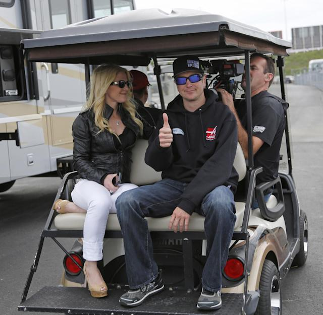 ADVANCE FOR WEEKEND EDITIONS, MAY 24-25 - FILE - In this May 17, 2014 file photo, Kurt Busch, right, gives a thumbs-up as he rides on a golf cart with his girlfriend, Patricia Driscoll, to prepare for the NASCAR Sprint All-Star auto race at Charlotte Motor Speedway in Concord, N.C. Busch will attempt to drive both the Indianapolis 500 and the NASCAR Coca-Cola 600 in Charlotte, NC. on Sunday. (AP Photo/Terry Renna, File)
