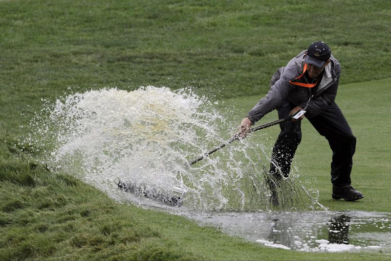 A course worker clears water from the 16th fairway during practice for the U.S. Open golf tournament at Merion Golf Club, Monday, June 10, 2013, in Ardmore, Pa. (AP Photo/Gene J. Puskar)