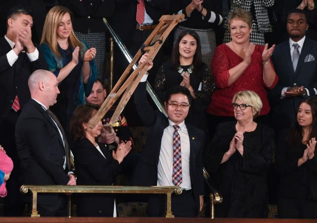 <p>North Korean defector Ji Seong-ho raises his crutches as Trump delivers the State of the Union address at the U.S. Capitol in Washington, D.C., on Jan. 30. (Photo: Saul Loeb/AFP/Getty Images) </p>
