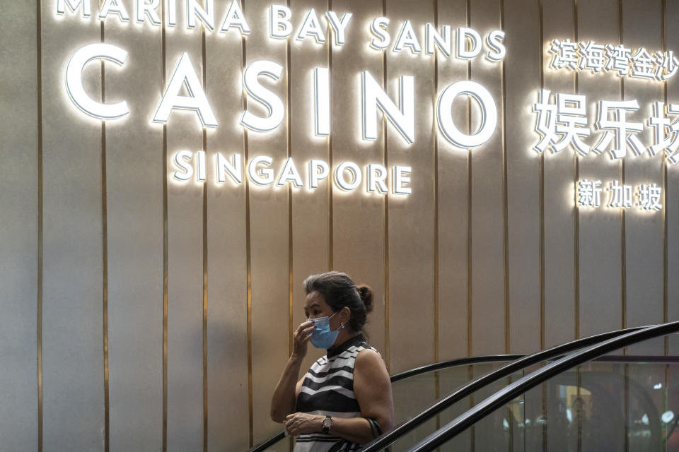 SINGAPORE, SINGAPORE - JULY 07: A woman wearing a protective face mask walks past a Marina Bay Sands Casino signage on July 07, 2020 in Singapore. Residents will go to the polls to elect members of parliament on July 10. (Photo by Ore Huiying/Getty Images)
