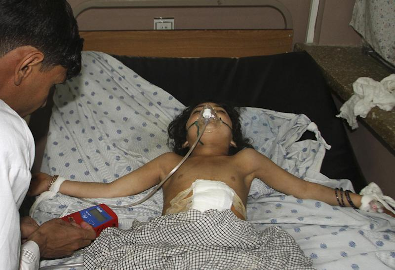 A young Afghan girl receives medical treatment at a hospital in Kandahar, Afghanistan, Friday, May 17, 2013 after a car bomb exploded inside an elite gated community linked to the family of Afghan President Hamid Karzai. Many people where killed and scores wounded, an official said.(AP Photo/Allauddin Khan)