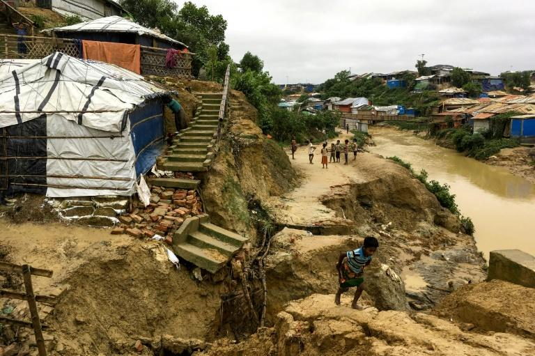 Rohingya children walk around debris from a landslide at Balukhali refugee camp